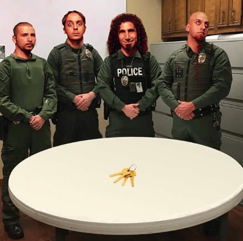 police department roast standing in front of system of a down