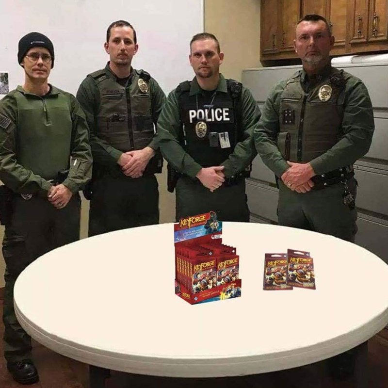 police department roast standing in front of a box of Keyforge