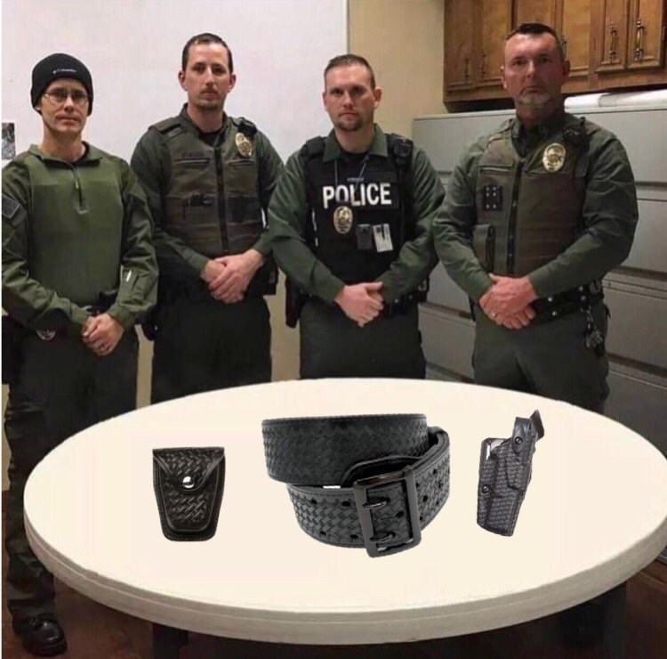 police department roast standing in front of a belt, cellphone and gun holster