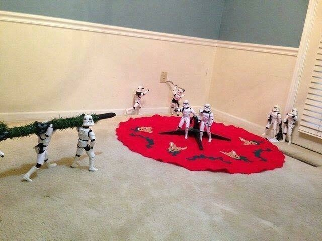picture of Stormtroopers carrying a tree while one is sticking a fork into an electric socket in the background