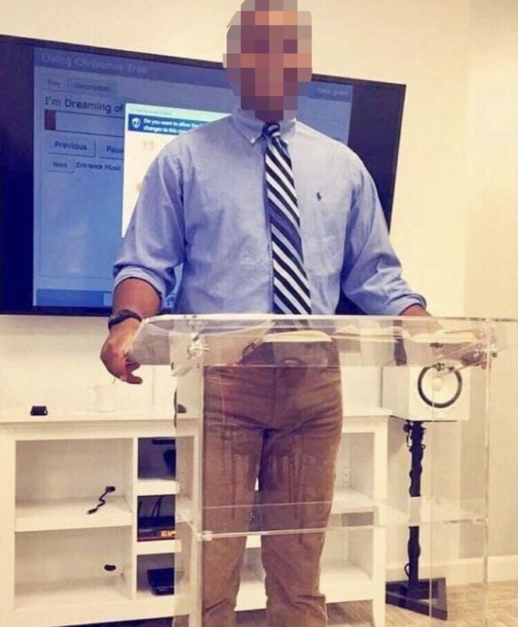 pic of man standing behind clear podium that is stained in a way that makes him look like he's peed himself