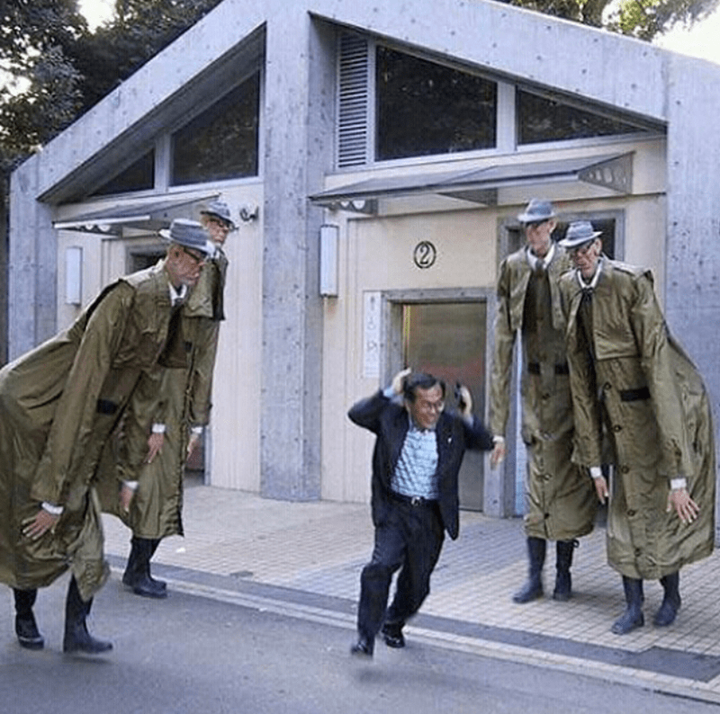pic of man running between group of abnormally tall men in matching trench coats