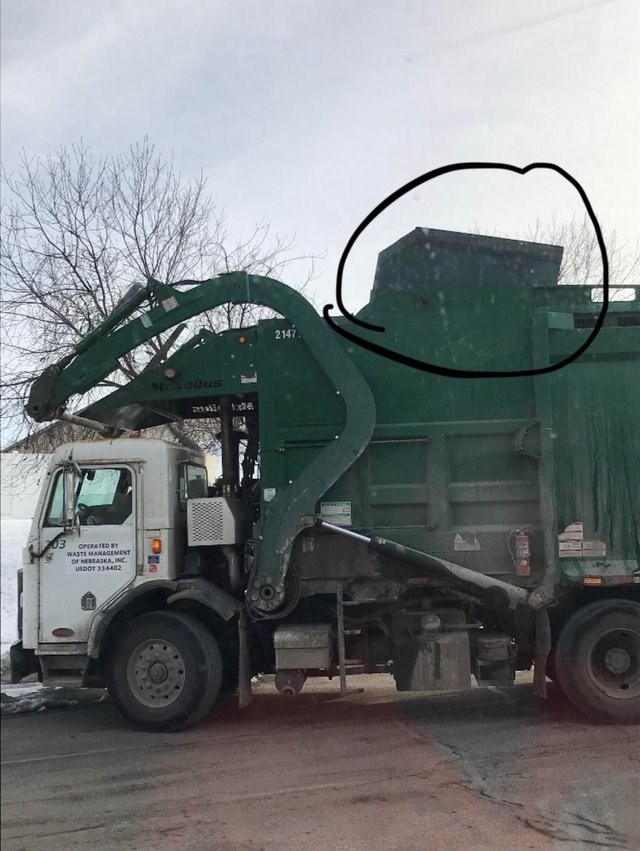 unfortunate moment when a dumpster was put into a garbage truck