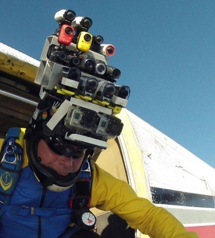 cursed image of man about to skydive from plane while wearing helmet covered in cameras