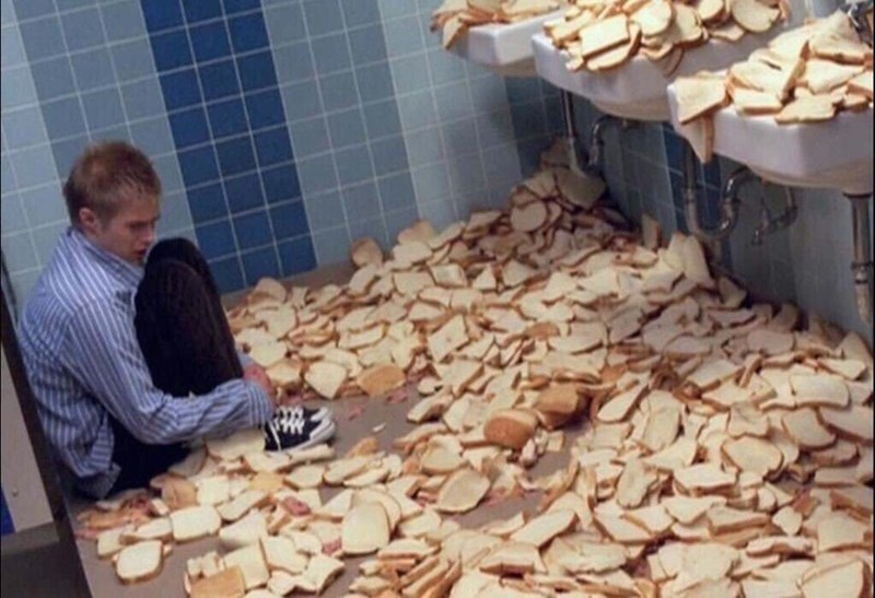 cursed image of man in fetal position surrounded by bread