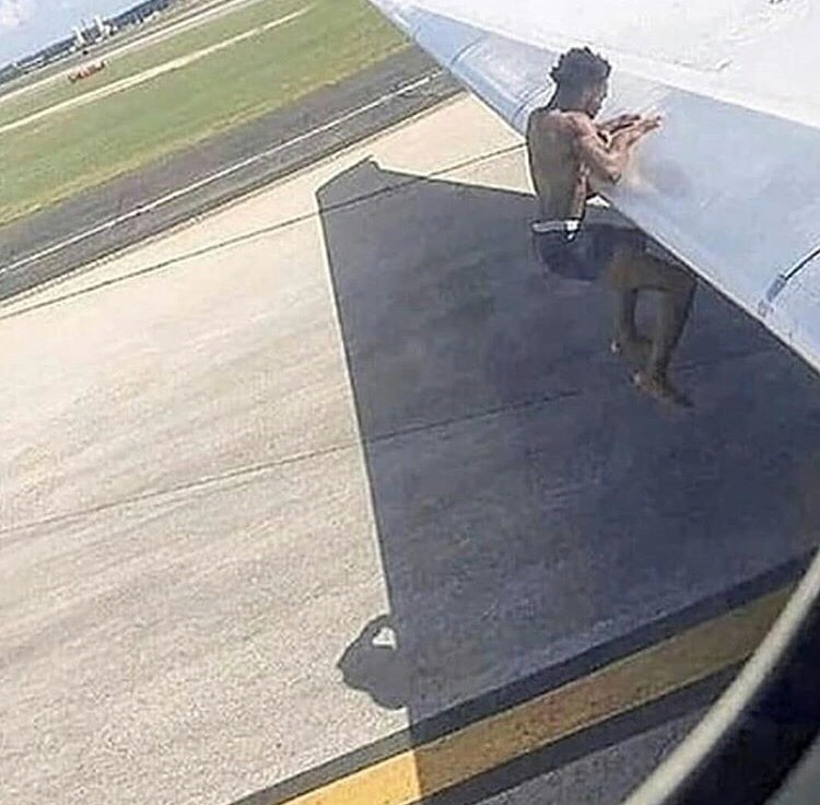 cursed_image of man on the wing of a plane as it tries to take off