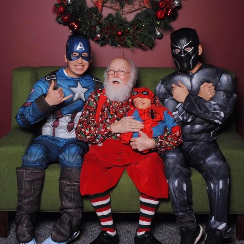 funny Santa pic of guys dressed in superhero costumes while sitting on Santa's lap