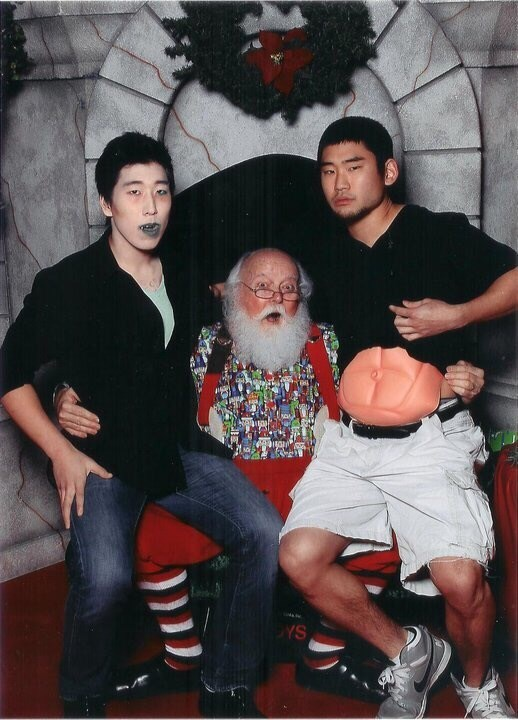 funny santa Pic of the two guys, one of which is wearing blue lipstick and the other is wearing a prosthetic six-pack under his shirt