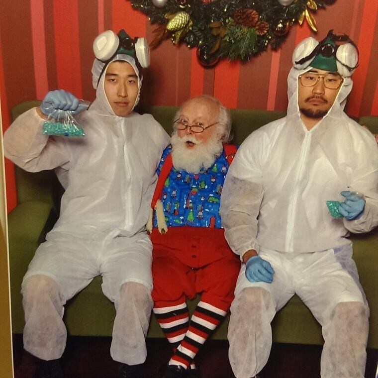 funny Santa pic of guys dressed in hazard costumes while sitting on Santa's lap