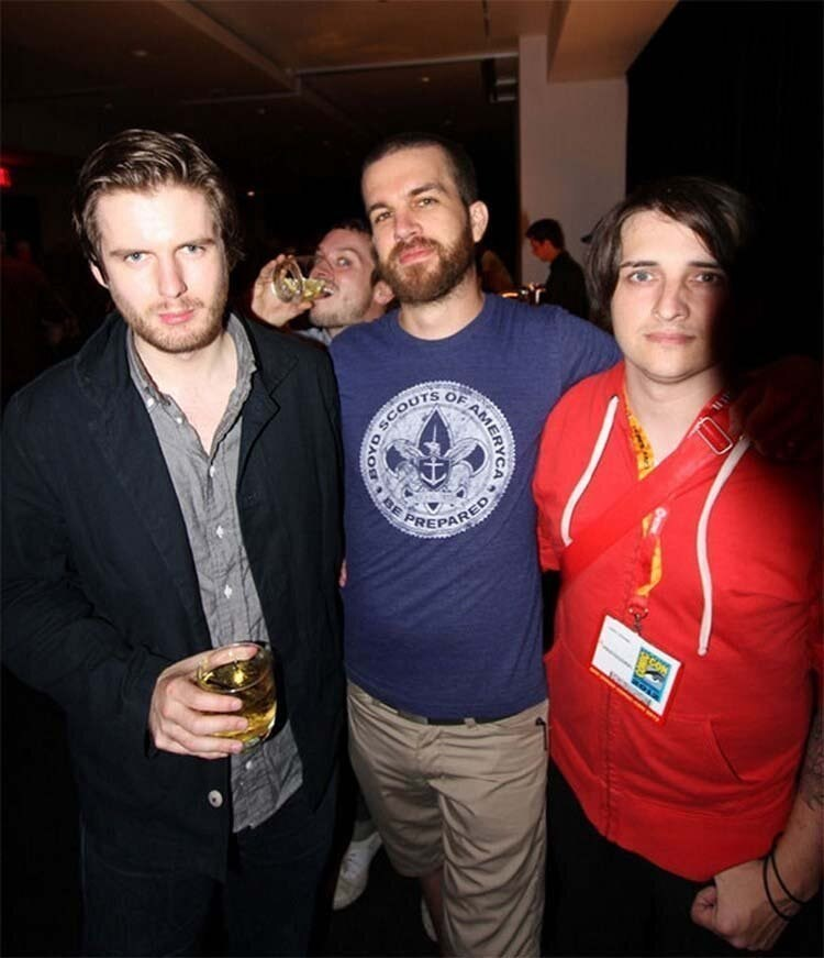 3 guys taking a pic photobombed by Elijah Wood
