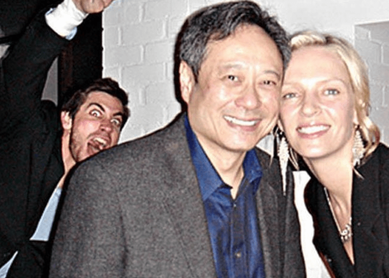 Uma thurman posing with a fan and photobombed by Jake Gyllenhaal