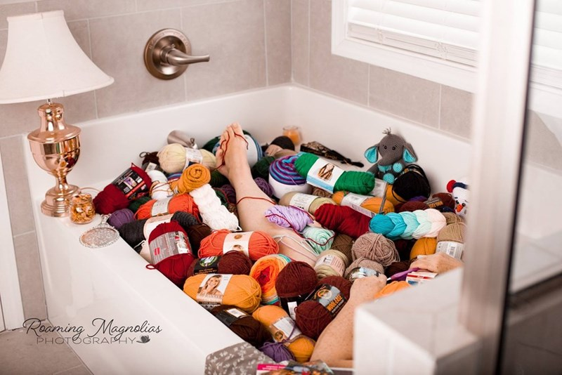 wholesome image of a bathtub filled with yarn and a mom in it