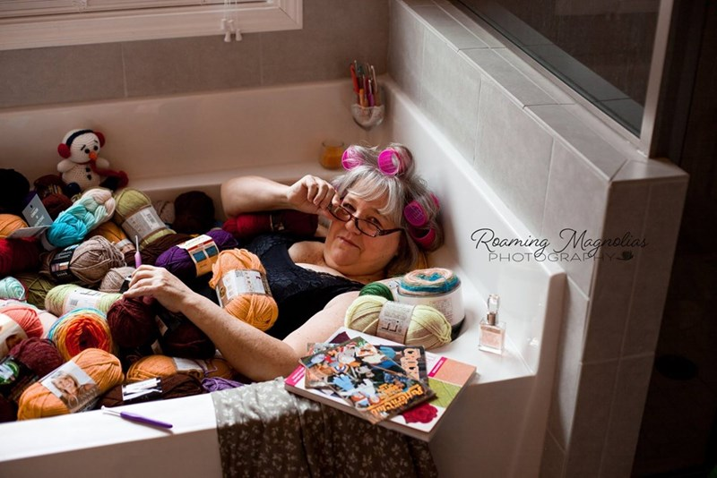 wholesome pic of a mom lowering her glasses while sitting in a tub of yarn