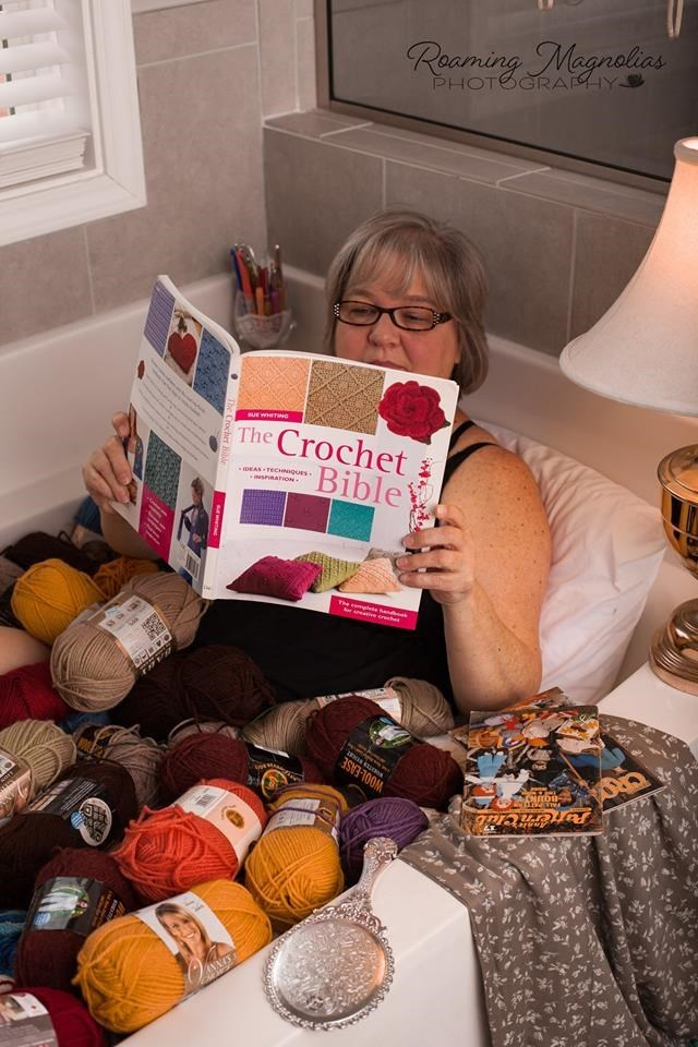wholesome pic of a woman reading a crochet bible while in a tub of yarn