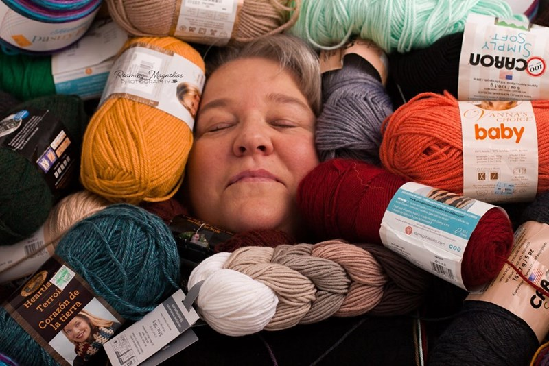 wholesome pic of a woman surrounded by yarn