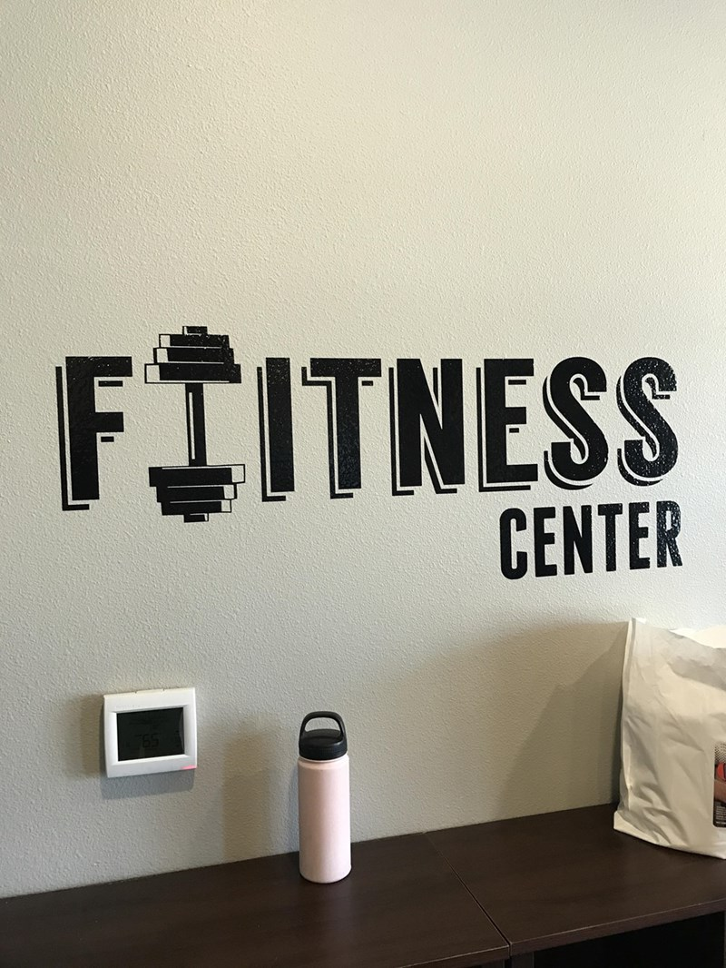 "crappy design of wall print that misspells the word ""fitness"""
