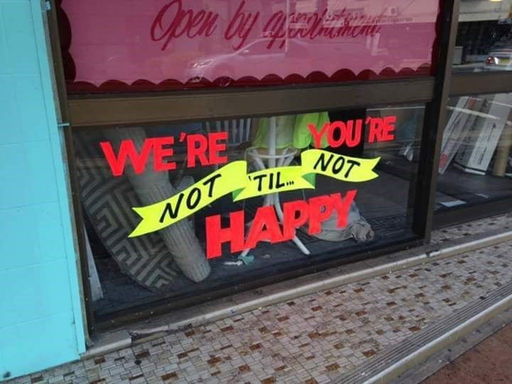crappy design of store window sign that is impossible to read in the correct order
