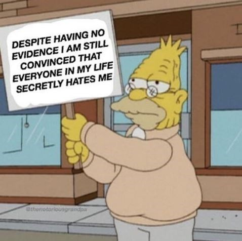 grampa Simpson holding a sign that says he's convinced everybody hates him