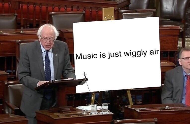 """bernie sanders next to a sign that says """"music is just wiggly air"""""""