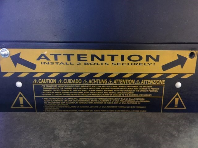Text - ATTENTION INSTALL 2 BOLTS SE CURELY! A CAUTION ACUIDADO ACHTUNGA ATTENTIONAATTENZIONE TO TRANSPORL ALWAYS REMOVE THE INDICATED BOLTS ON SACK OF LOWER CABINET AND LOwER THE BACaox FOEWARD ONTO THE CABN DAMAGE, DO NOT TRANSNORT THS MACON OR ANY PNALL MACHINE WITH THE BACKBOK IN THE UPGHT POsmON ATTENTION wN SETTg UP TE GA BASE THE BACKOK AND STALL BOLTS SECURELY PARURE TO DO ANY OP THE AaOVE MAY RESULT IN PERSONAL INJURY OR DAMAGE TO THE BACKOK AND CARIET OF PROTECTRvE MATERAL ETWEEN THE BA