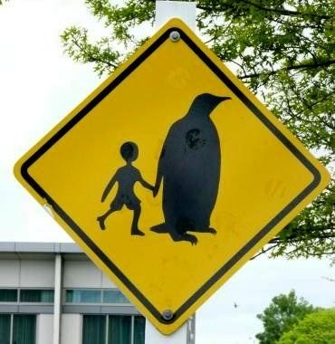 road sign showing a giant penguin holding a human child's hand