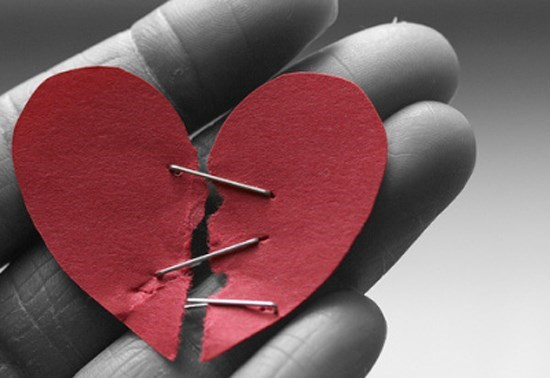 black and white pic of a hand holding a red paper heart torn in the middle and held together by pins