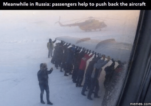 """Caption that reads, """"Meanwhile in Russia: passengers help to push back the aircraft"""" above a pic of a bunch of people pushing the wing of an airplane"""