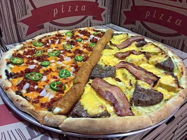 Pic of a disgusting-looking pizza that's half taco pizza and half scrambled eggs and sausage, with mozzarella sticks dividing it