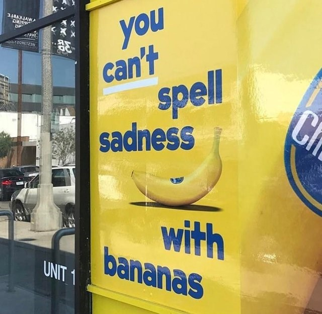 Yellow sign in store window- you can't spell sadness with bananas