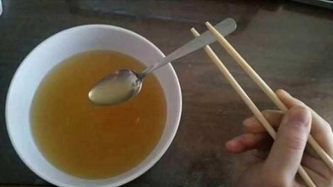 cursed image - using chopsticks to hold a spoon