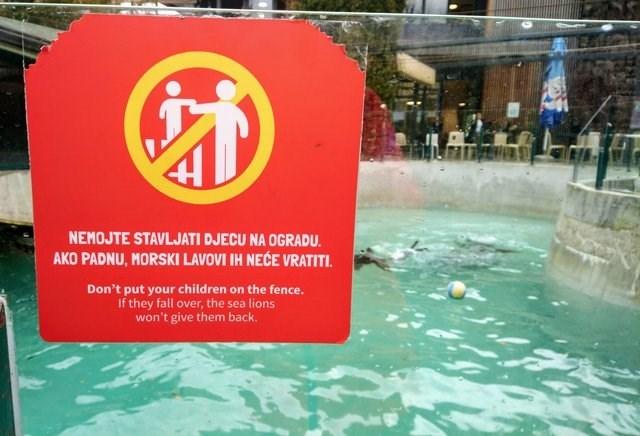 Sign - NEMOJTE STAVLJATI DJECU NA OGRADU. AKO PADNU, MORSKI LAVOVI IH NECE VRATITI Don't put your children on the fence. If they fall over, the sea lions won't give them back.