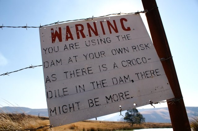 Text - WARNINC YOU ARE USING THE DAM AT YOUR OWN RISK AS THERE IS A CROCO- DILE IN THE DAM, THERE MIGHT BE MORE.