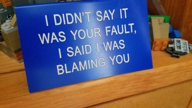 blur sign on desk saying I DIDN'T SAY IT WAS YOUR FAULT I SAID IWAS BLAMING YOU