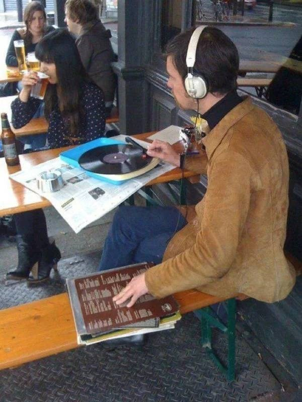 Pic of a guy listening to a turntable at a table with his headphones on