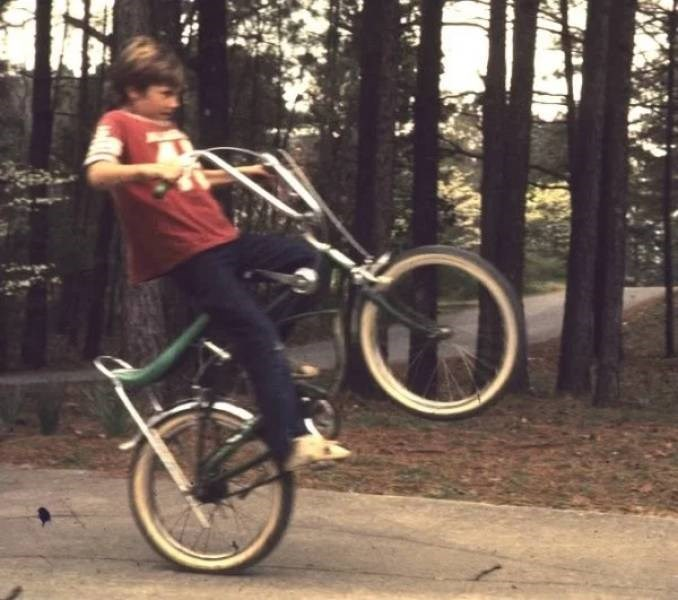 nostalgic pic of kid doing a front wheel lift on a bike