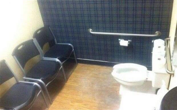 cursed_image - toilet in room with chairs