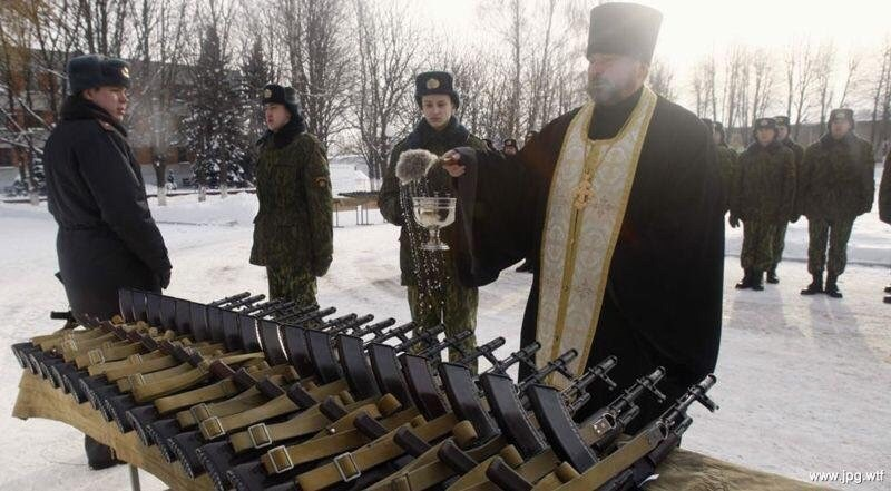 Pic of an orthodox priest blessing a row of rifles with holy water