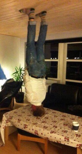 man doing a headstand on a table