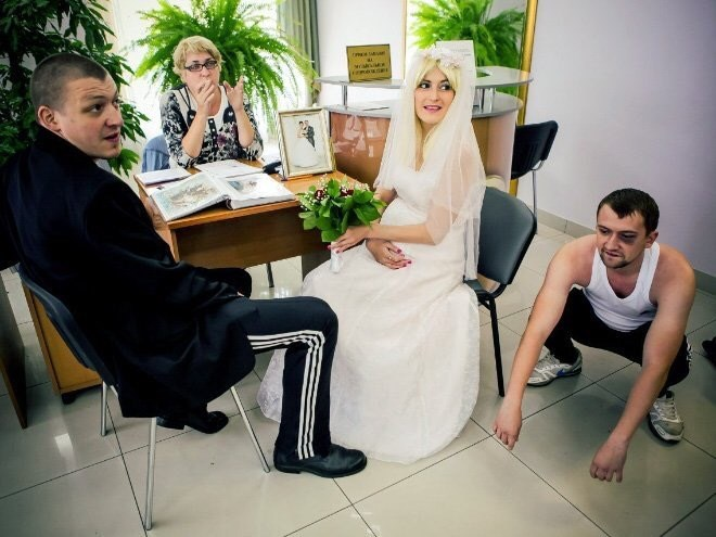bride and groom and a man squatting near them