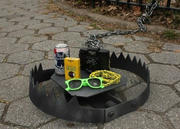 Pic of a bear trap with sunglasses, PBR, cigarettes and a bike chain inside of it