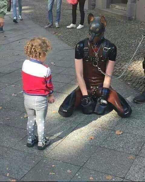 cringey meme with kid approaching person dressed in fetish dog latex suit