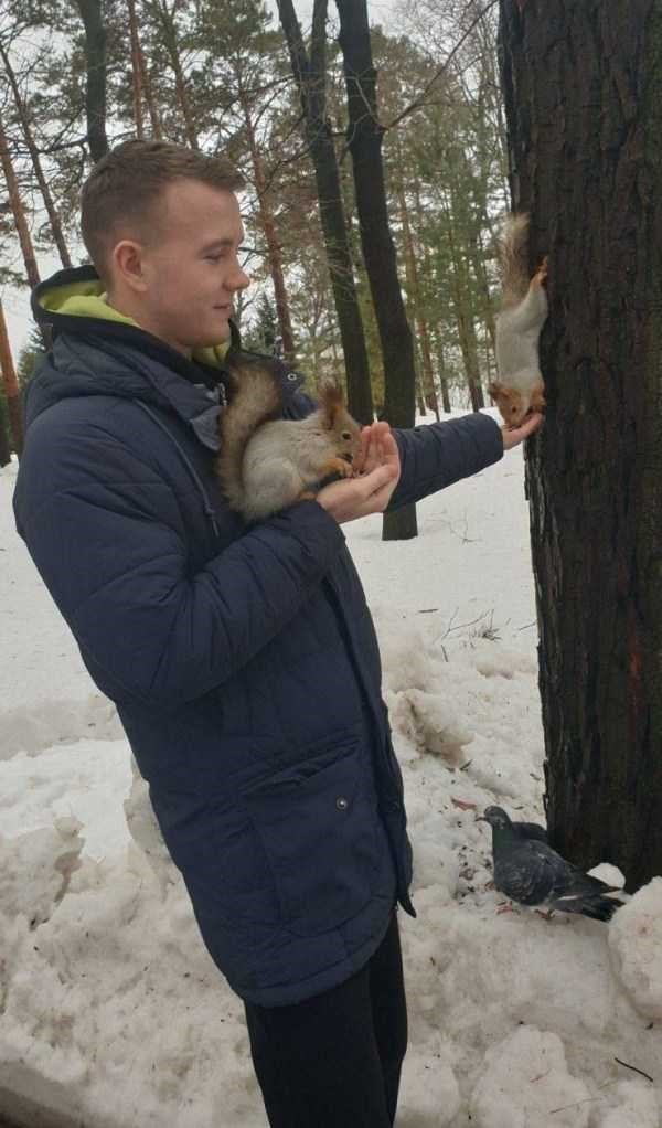 man holding squirrels in the snow against a tree