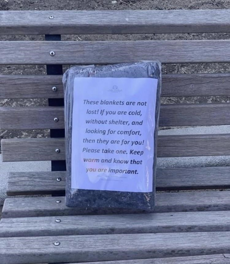 "Package on a park bench that reads, ""These blankets are not lost! If you are cold, without shelter, and looking for comfort, then they are for you! Please take one. Keep warm and know that you are important"""