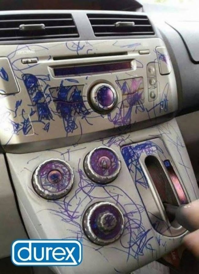 Pic of a car stereo that's been drawn on with sharpie by a kid with a Durex logo in the corner