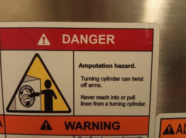 Sign - A DANGER Amputation hazard. Turning cylinder can twist off arms. Never reach into or pull linen from a turning cylinder. A WARNING AAD