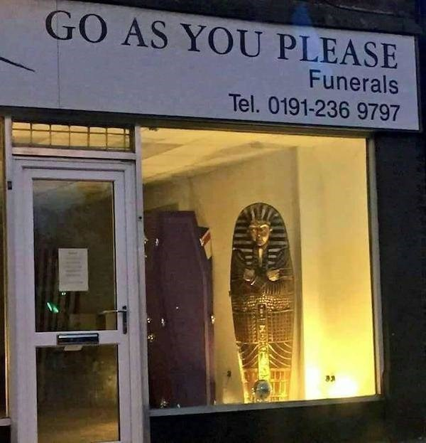 """Pic of a store called """"Go As You Please Funerals"""" with a sarcophagus in the window"""