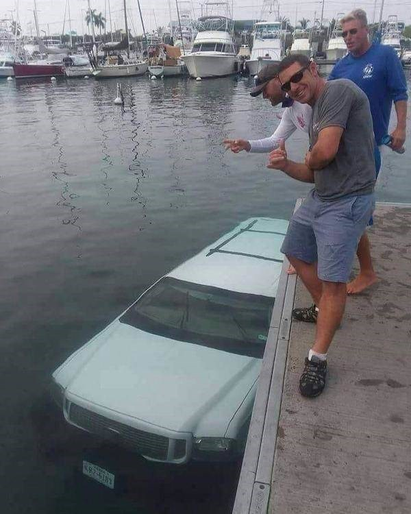 Pic of some guys posing for the camera next to a car that has gone underwater