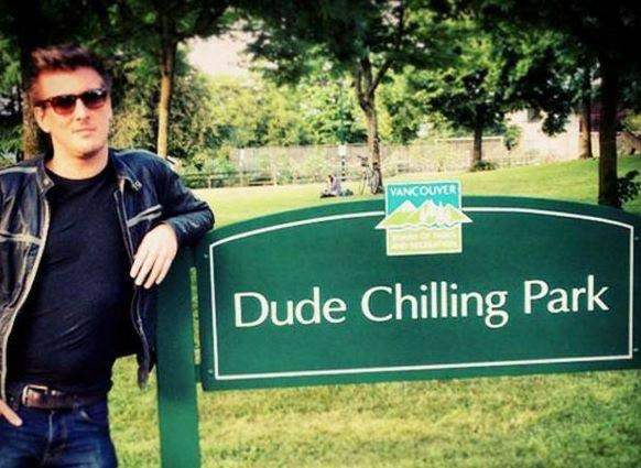 """Pic of a guy standing next to a sign that reads, """"Dude Chilling Park"""""""