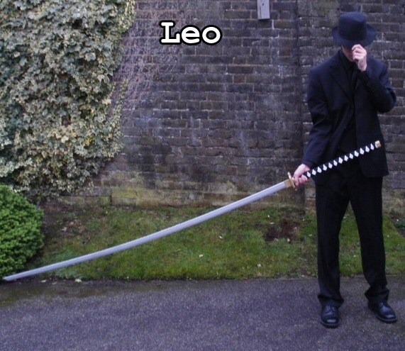 guy in black suit tilting hat holding long sword to the side