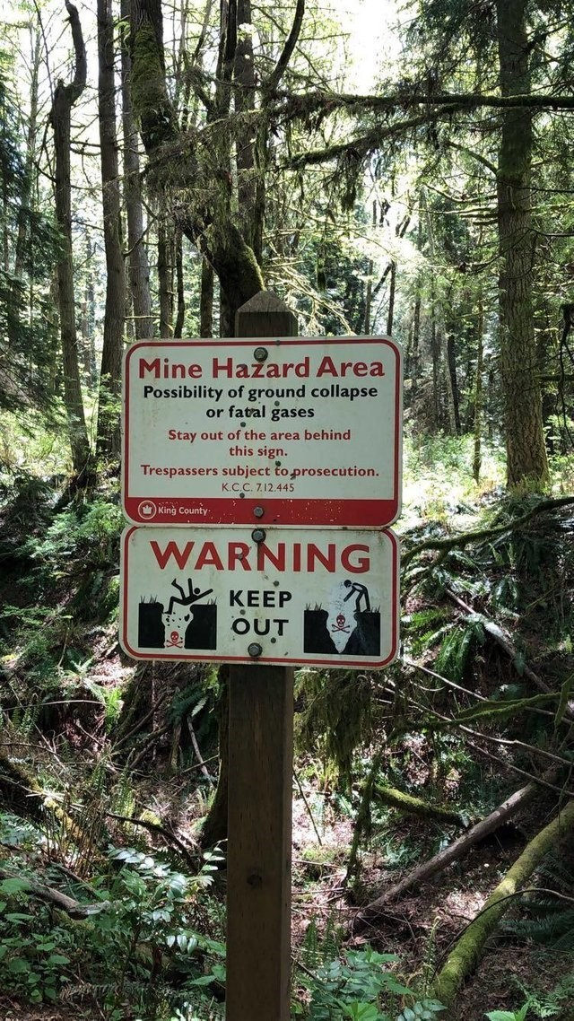 Nature reserve - Mine Hazard Area Possibility of ground collapse or fatal gases Stay out of the area behind this sign. Trespassers subject to prosecution. K.C.C. 712.445 King County WARNING КЕЕР OUT